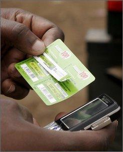 A Kenyan man loads airtime on his Safaricom phone
