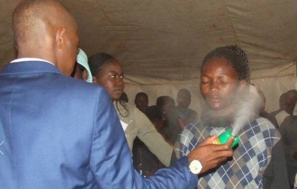 Church Pastor spraying pesticides to its worshipers
